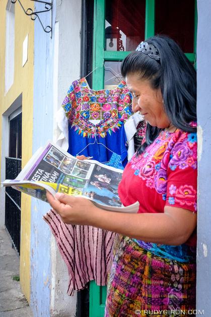 Rudy Giron: Antigua Guatemala &emdash; Smiling Maya woman reading newspaper