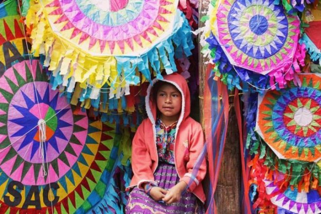 Mayan girl ushers passers-by into a kite shop for All Saints' Day by Rudy Giron