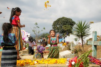 Mayan girls play around a tombstone for All Saints' Day by Rudy Giron