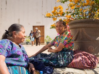 Two Maya women talk to each during the lunch break steps away from the entrance of the Cathedral ruins in Antigua Guatemala BY RUDY GIRON