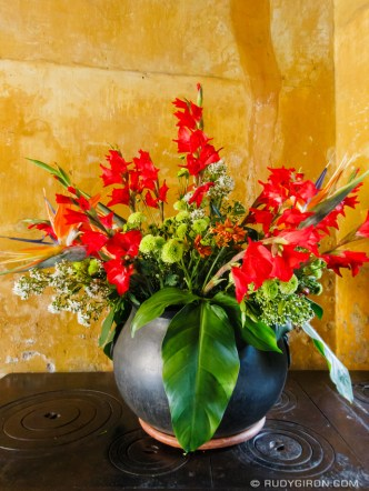 PHOTO STOCK: vase with exotic flowers against rich yellow wall
