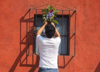 Teenager places a Palm Sunday bouquet in his window crate BY RUDY GIRON