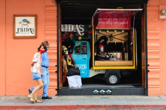 Couple with face masks walks by a Tuk Tuk Bar with Mexican Decoration