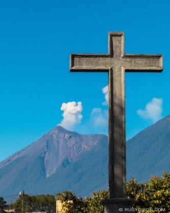 PHOTO STOCK: Fuego Volcano's Eruption Framed with a Cross as seen from San Pedro Las Huertas, Antigua Guatemala