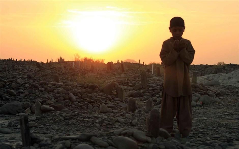 Ένα αγόρι προσεύχεται στον τάφο συγγενών του που έχασαν τη ζωή τους από τον καταστροφικό σεισμό που έπληξε το νοτιοδυτικό Πακιστάν.