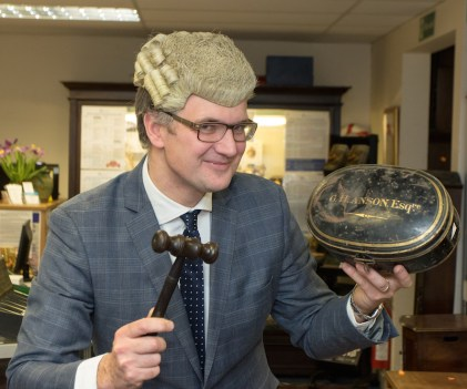 Auctioneer Charles Hanson wears the antique wig