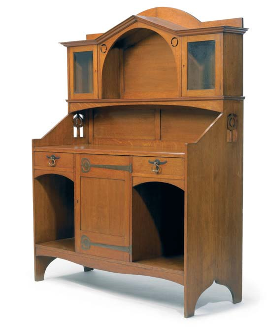Oak sideboard of c.1900 made by J.S. Henry to a design by E.G. Punnett. With copper fittings and Voysey-style hinges to the lower door. (Liberty's)