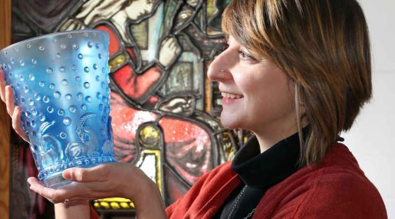 Elstob & Elstob Specialist and general valuer, Melanie Saleem, is pictured examining a Rene Lalique 'Ajaccio' vase designed in 1938, with an Arts & Crafts stained and leaded glass window in the background