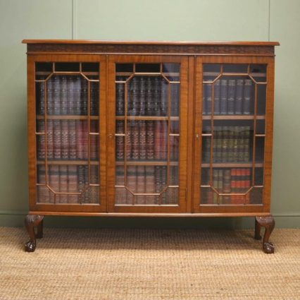 Edwardian walnut Chippendale design bookcase by Maple & Co., with blind fretwork carved frieze, astragal glazed doors
