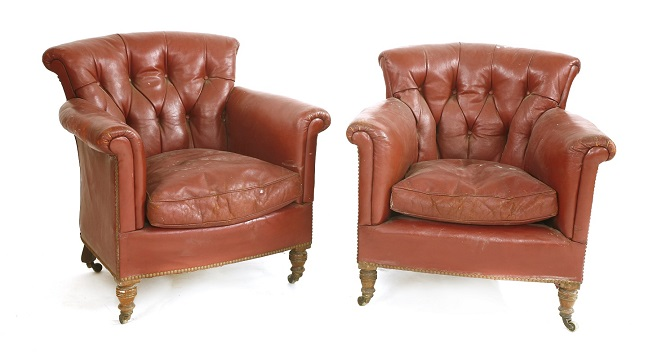 A pair of Victorian crimson leather armchairs