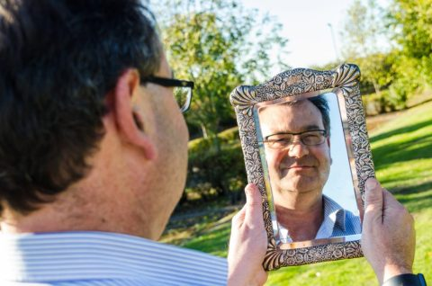 Auctioneer Richard Winterton with mirror that belonged to Captain of The Titanic