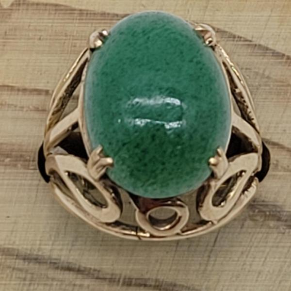 amazingly ornate 9ct yellow gold ring with a large polished oval jade stone claw set to the centre