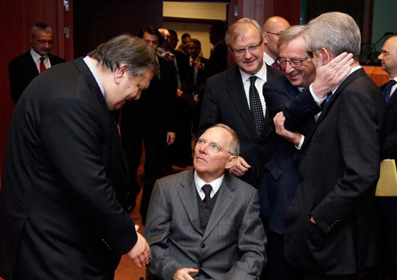 Evangelos Venizelos prepares to shake hands with Wolfgang Schaeuble while Mario Monti is greeted by Jean-Claude Juncker in Brussels