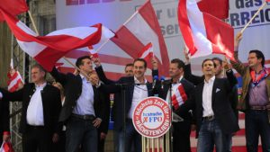 TO GO WITH AFP STORY BY SIMON STURDEE Heinz-Christian Strache (C) candidate of the Freiheitliche Partei Oesterreichs FPO Party (Freedom Party of Austria) waves flags during a meeting of the FPO political party in Klagenfurt on September 14, 2013 ahead of the Austrian legislative elections taking place on September 29, 2013. AFP PHOTO / ALEXANDER KLEIN