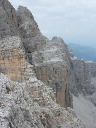 Crux section on Bocchette Alte, see climbers descending across unprotected rib after high level traverse behind.
