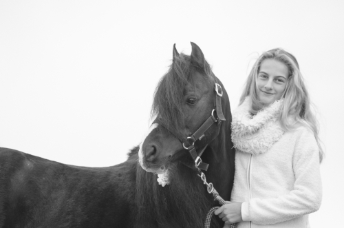 Smiling girl and black pony stallion