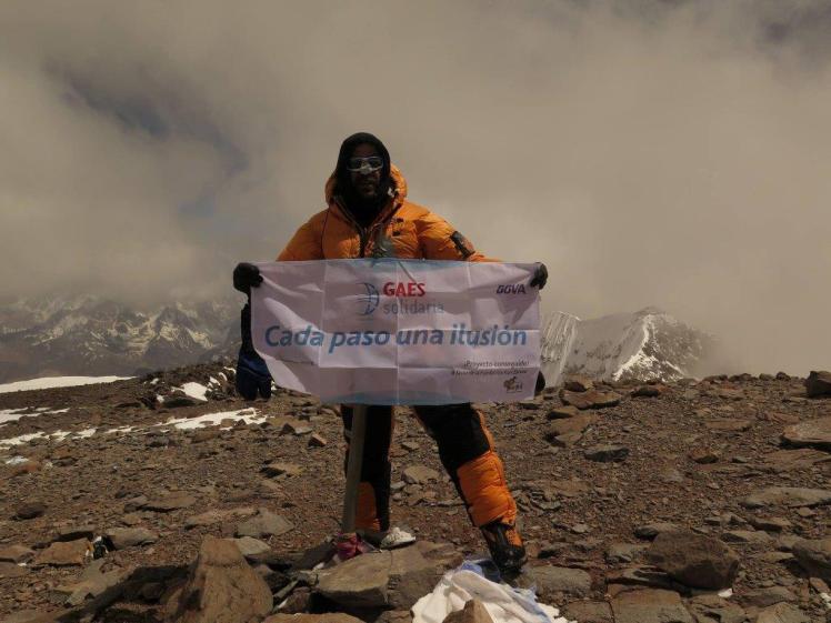 Antonio Gassó en la cima del Aconcagua junto a una pancarta de GAES Solidaria