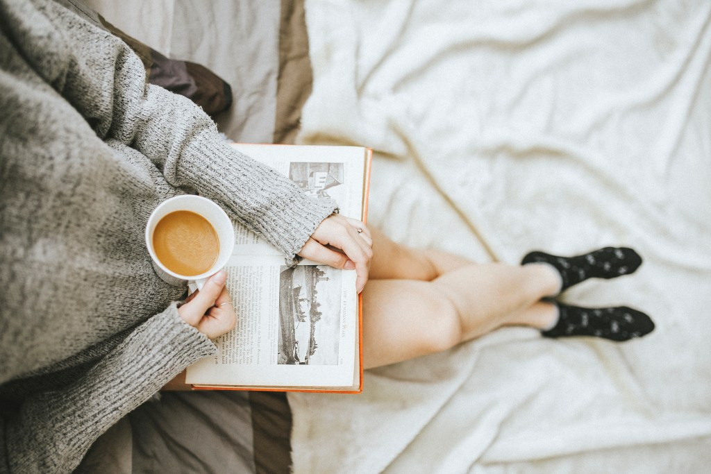 woman reading with coffee in hand