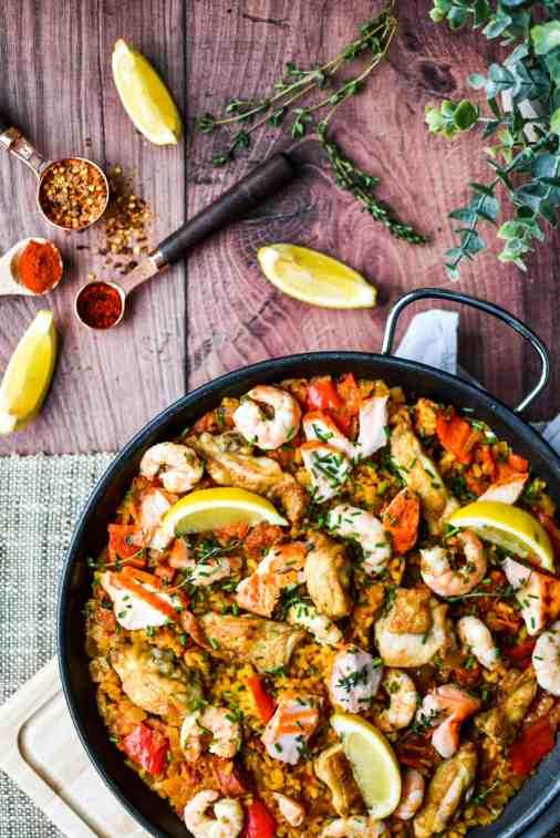 Paella pan full of salmon and meat paella