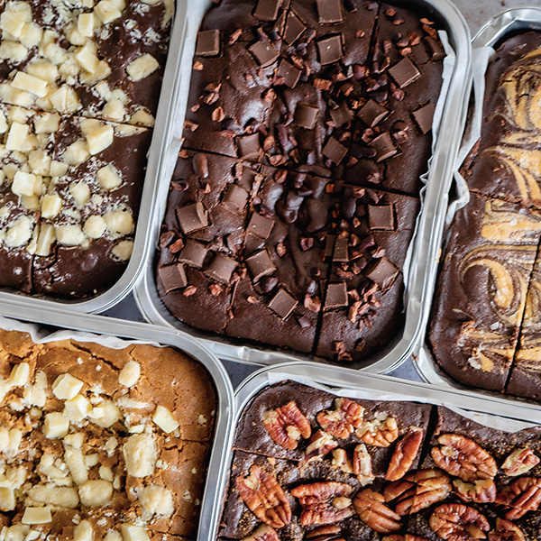 5 different flavored brownies on trays