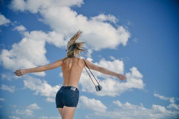 夏空とカメラをぶら下げた女性