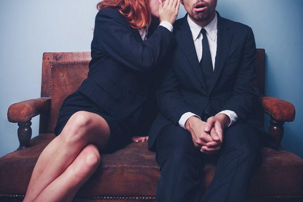 他人の悪口を耳打ちする女性