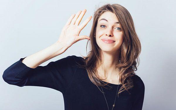 手をあげて挨拶をする女性