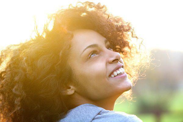 夕暮れの空を見上げて微笑む女性