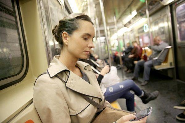 帰りの電車でメールを打つ女性