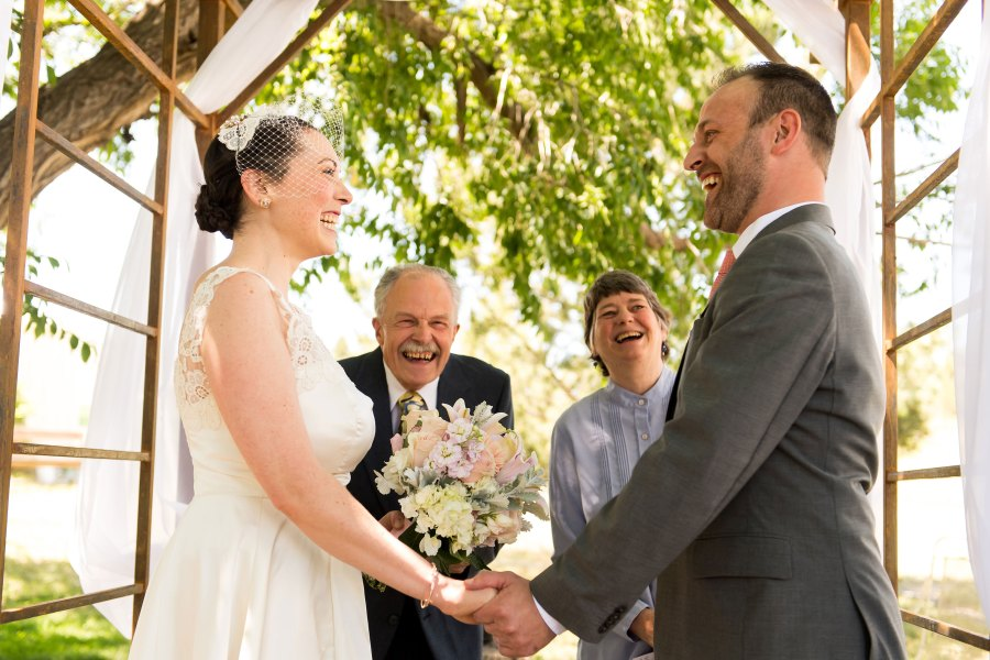 A couple holds hands during a backyard wedding ceremony in Colorado.