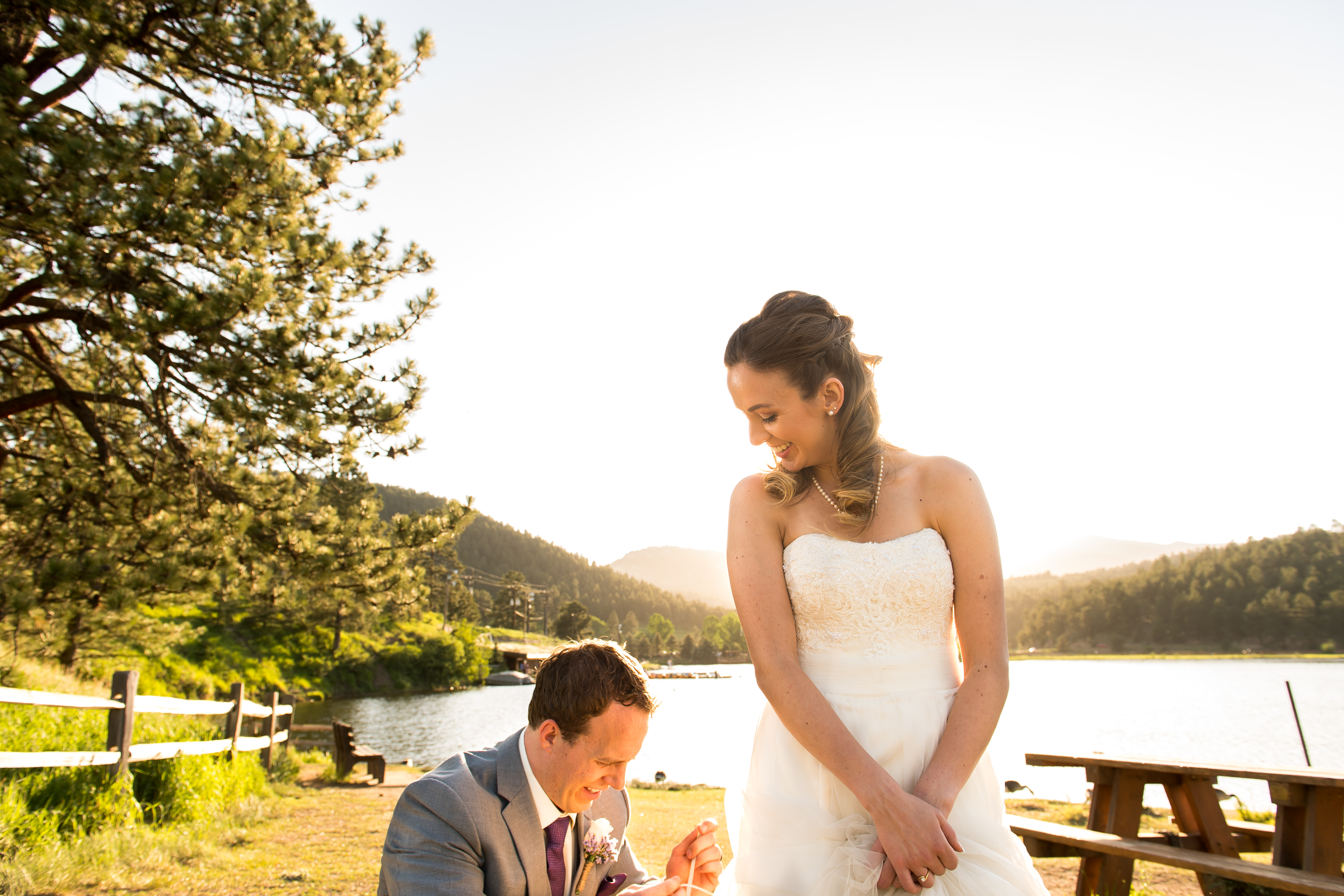 Evergreen Lake House wedding pictures of groom fixing bride's dress