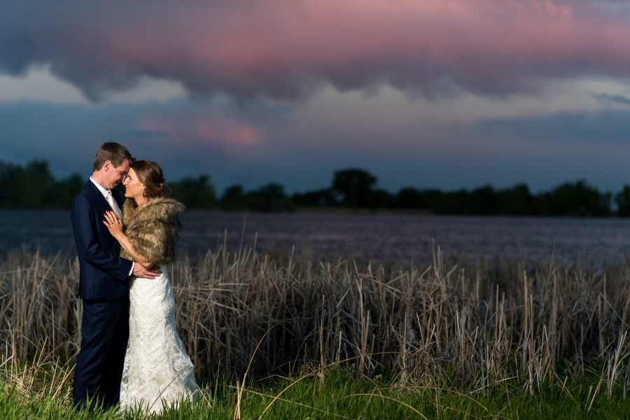 Bride and groom pose at sunset during a backyard wedding in Colorado.