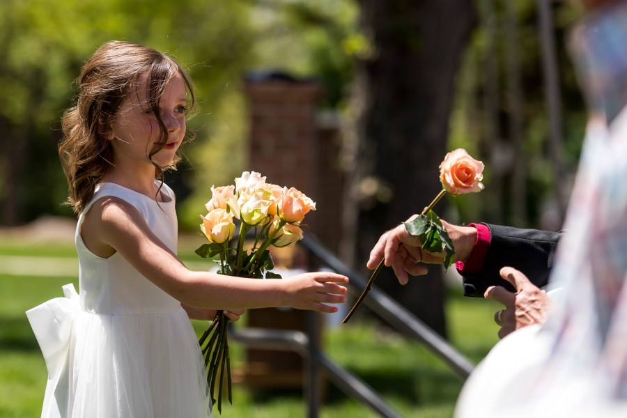A flower girl hands out flowers during an Our Lady of Lourdes Denver wedding.