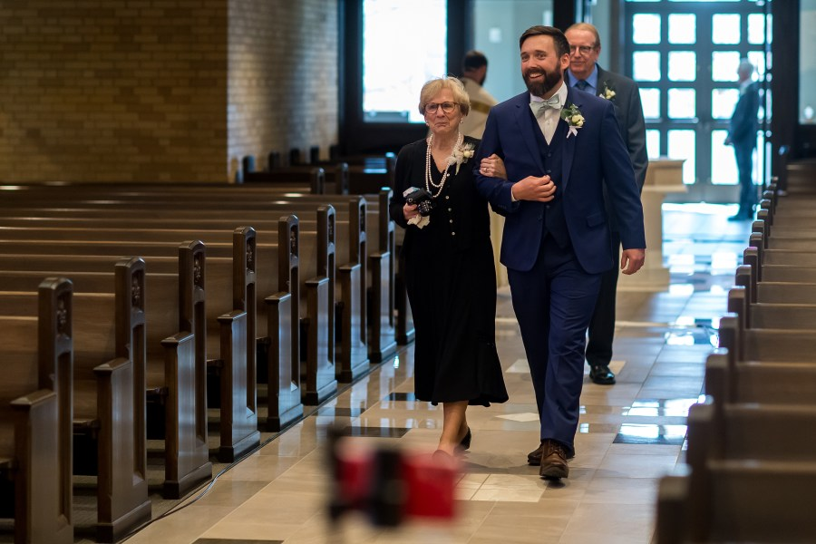 Groom walks his mother down the aisle during a wedding Mass at Our Lady of Lourdes Catholic Church in Denver, Colorado.