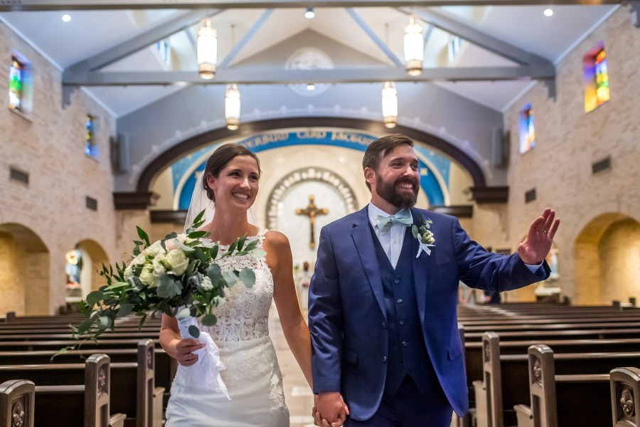 Bride and groom acknowledge friends at Our Lady of Lourdes Catholic Church in Denver, Colorado, after their wedding