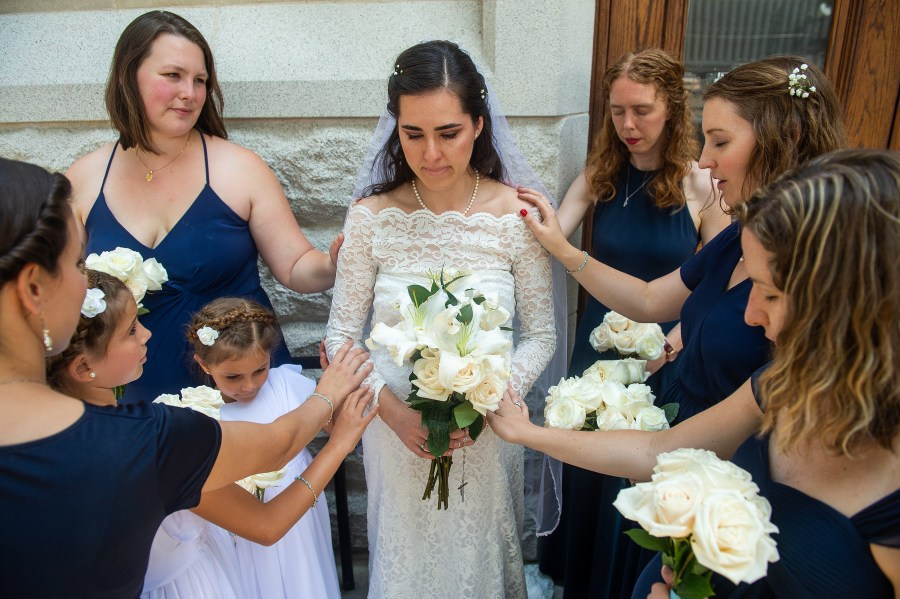 Bride is prayed over while crying before her wedding at the Cathedral Basilica of the Immaculate Conception in Denver, Colorado.