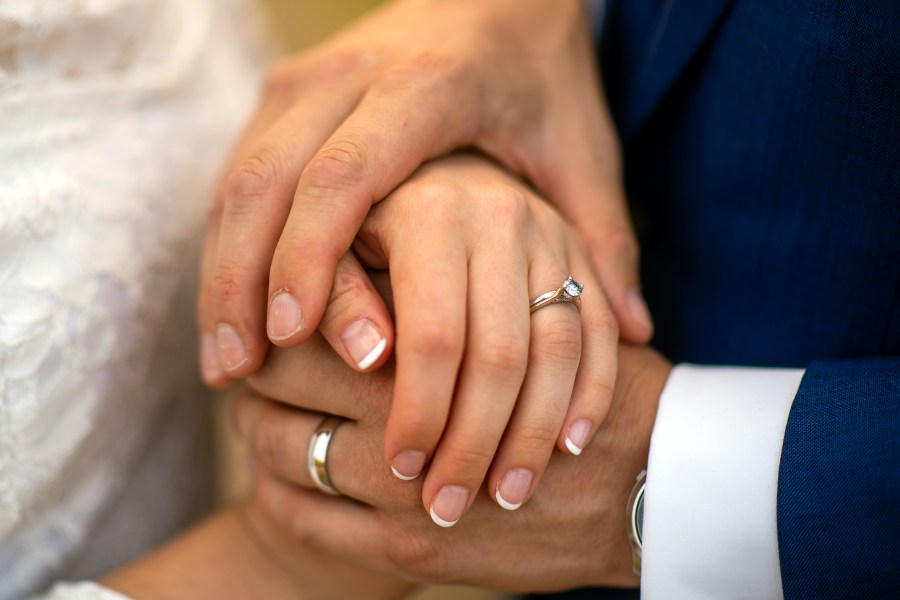 Bride and groom hold hands during their wedding portrait session at Bear Creek Lake Park in Lakewood, Colorado.
