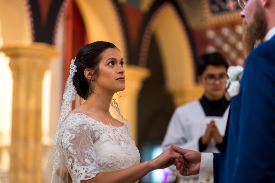 Bride looks on during her wedding at Our Lady of Mt. Carmel in Littleton, Colorado.