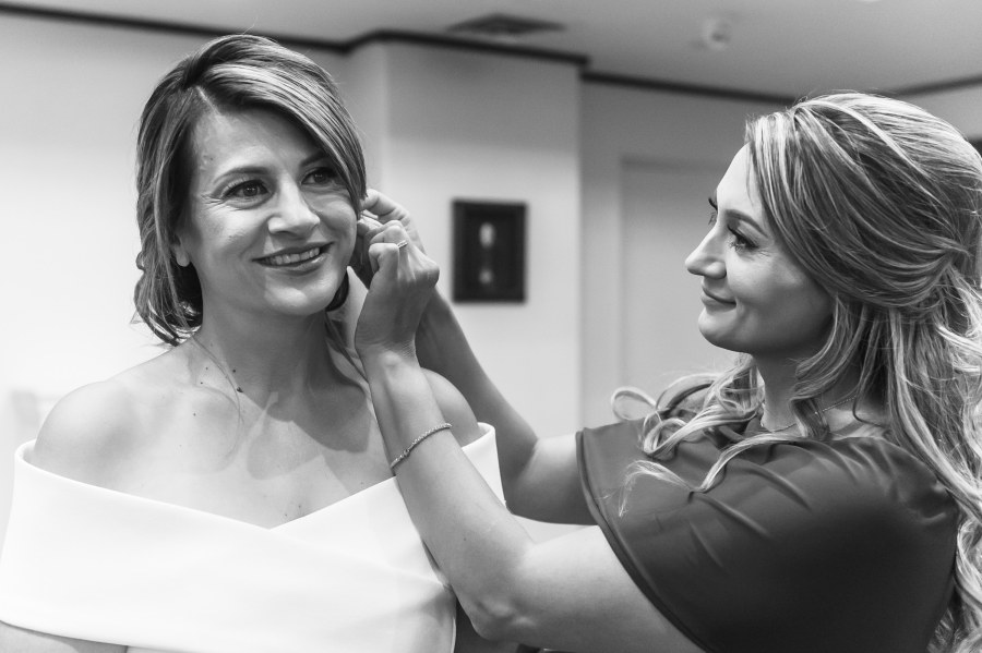 The bride is pinned with earrings before a wedding Mass at St. Joseph Catholic Church in Fort Collins, Colorado, on August 8, 2020.