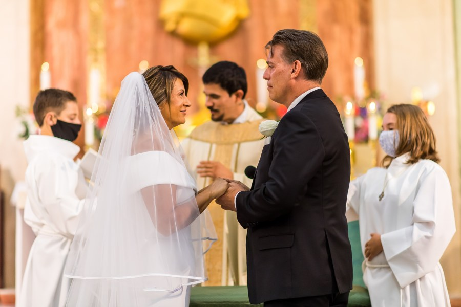 The bride and groom look on during a wedding Mass at St. Joseph Catholic Church in Fort Collins, Colorado, on August 8, 2020.