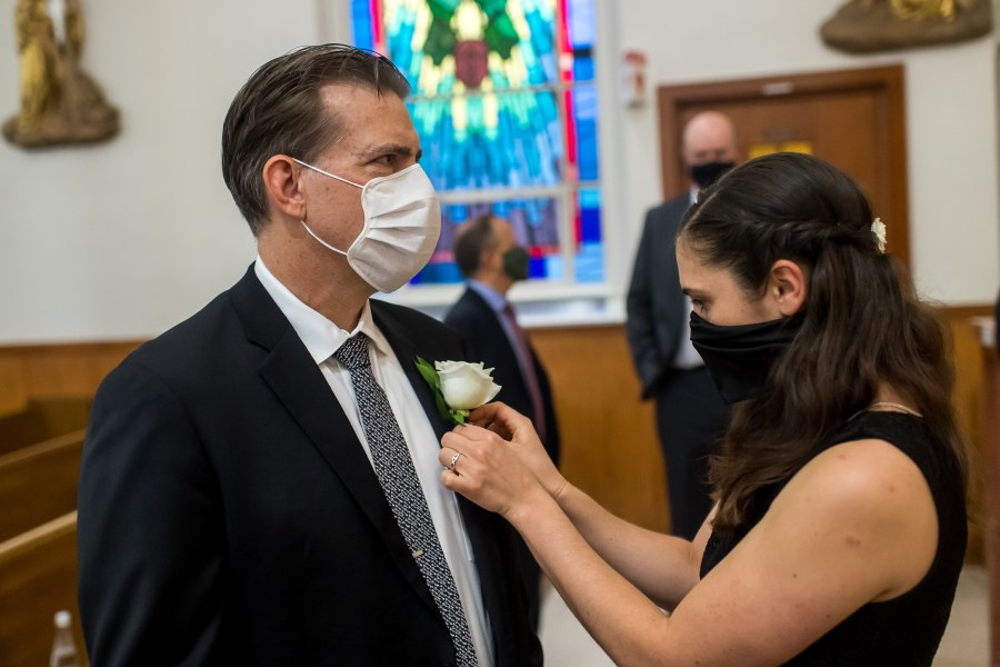 The groom is pinned with his boutonniere before a wedding Mass at St. Joseph Catholic Church in Fort Collins, Colorado, on August 8, 2020.