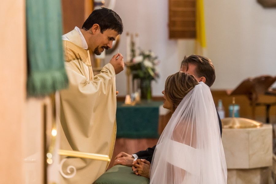 Bride and groom prepare to receive communion during their St. Joseph Catholic Church wedding on August 8, 2020, in Fort Collins, Colorado.