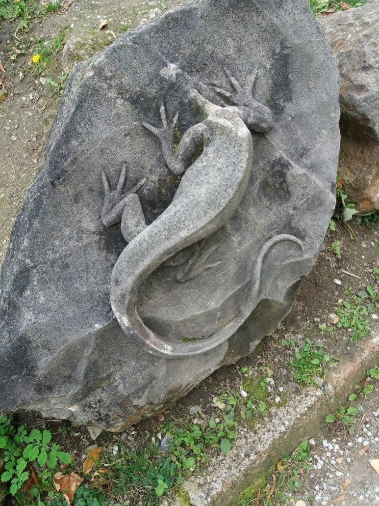Headless stone lizard in the gardens of Hotel Palota Lillafüred