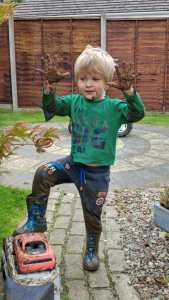 Small boy covered in mud