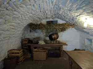 Barrels and boxes stored in a whitewashed stone cellar