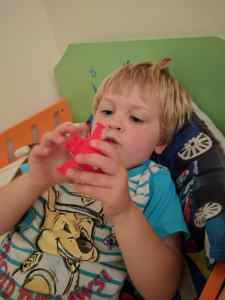 Boy playing with red plane toy in bed