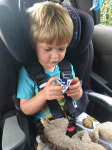 Boy in car seat playing with plane toy