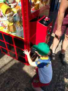 Retrieving a cuddly toy from a red arcade grab game