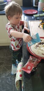 Boy decorating home baked cake