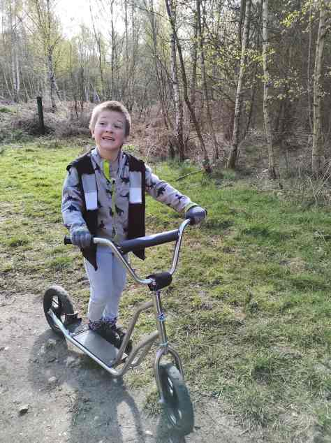 boy on scooter in the woods